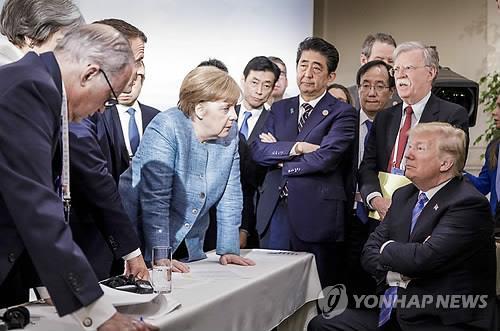 캐나다 퀘벡주 샤를부아에서 지난해 6월 9일(현지시간) 열린 주요 7개국(G7) 정상회의에서 도널드 트럼프 미국 대통령(오른쪽)이 팔짱을 낀 채 의자에 앉아 있고 앙겔라 메르켈 독일 총리(가운데 왼쪽)가 두 손으로 테이블을 누르며 트럼프 대통령을 내려다보고 있다. [AP=연합뉴스 자료사진]